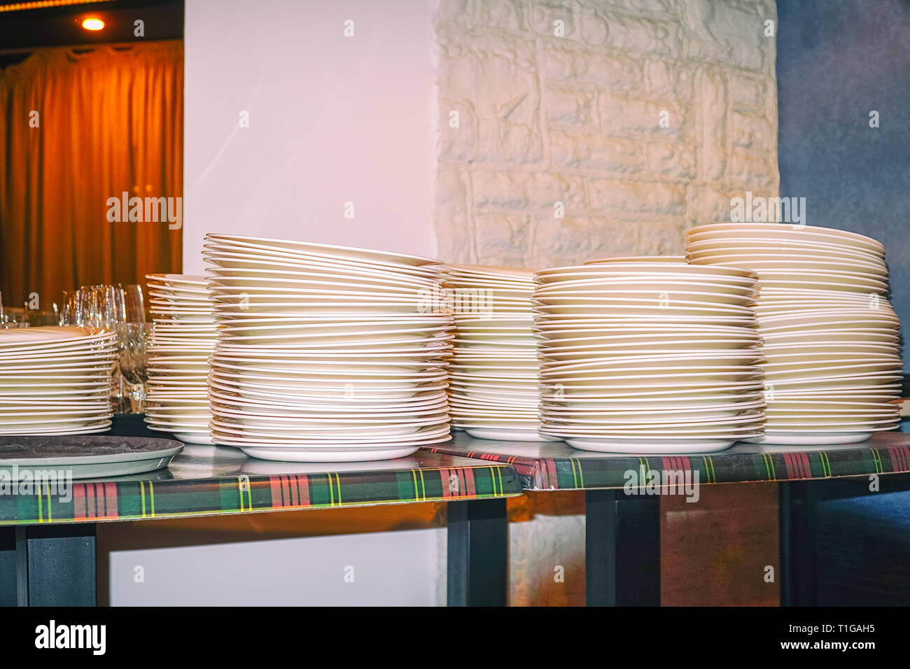 Clean white plates stacked on table - Stock Image
