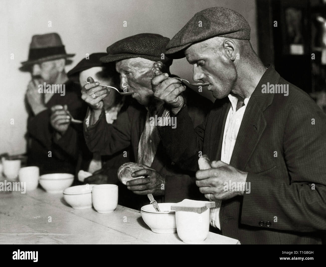 Men eating bread and soup in a bread line during The Great Depression in the U.S., circa 1929  File Reference # 1003_730THA - Stock Image