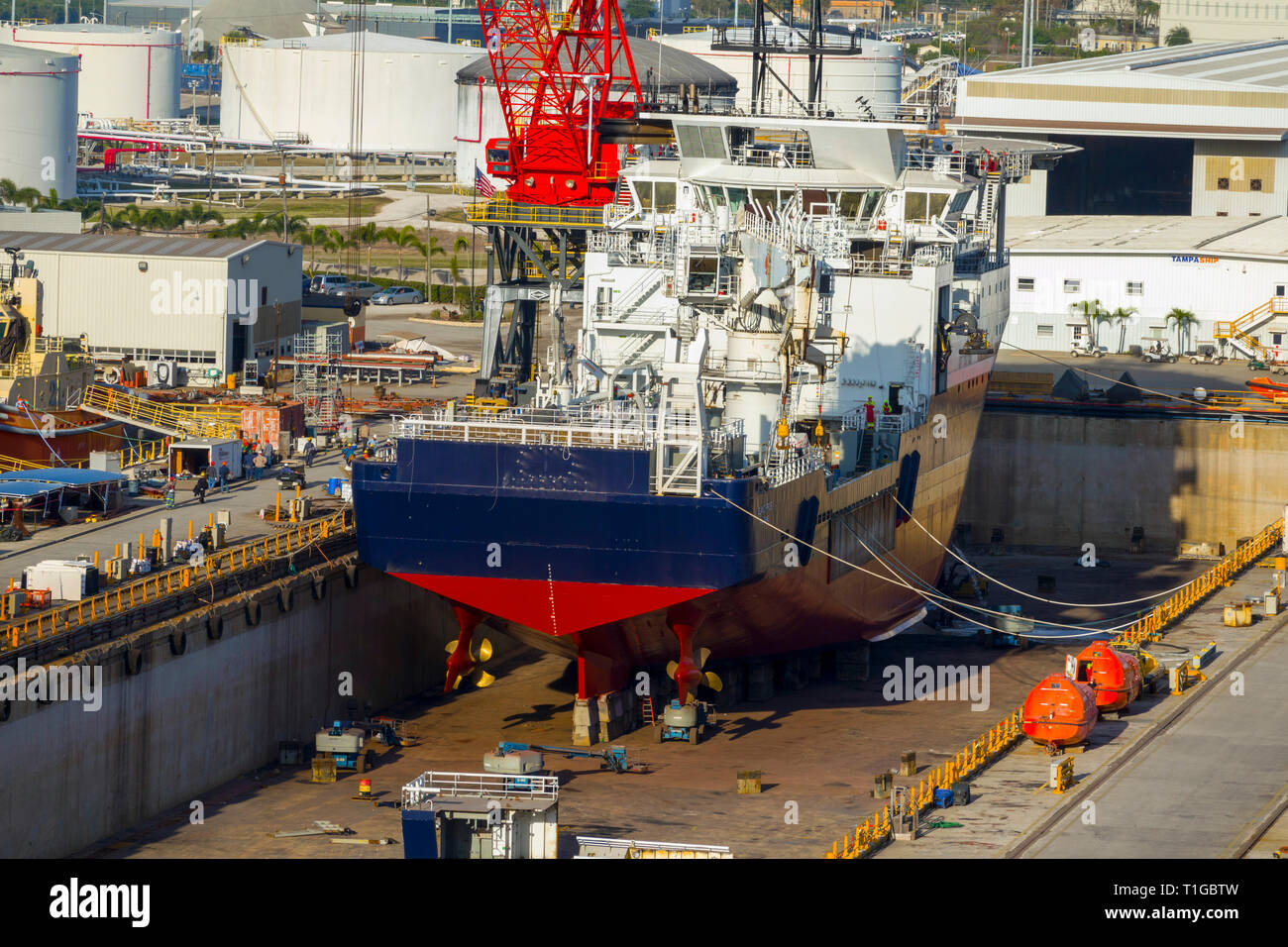 Ship in dry dock for repairs and maintenance  Tampa Florida A dry dock (sometimes dry-dock or drydock) is a narrow basin or vessel that can be flooded - Stock Image