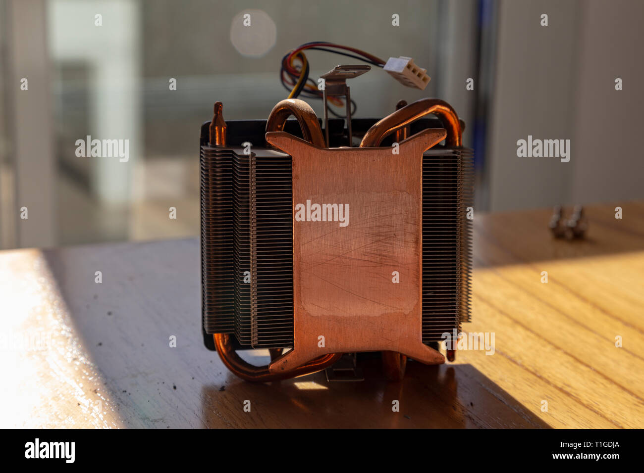CPU heat sinker from a PC. Copper heatsinker with a fan for cooling the processor - Stock Image