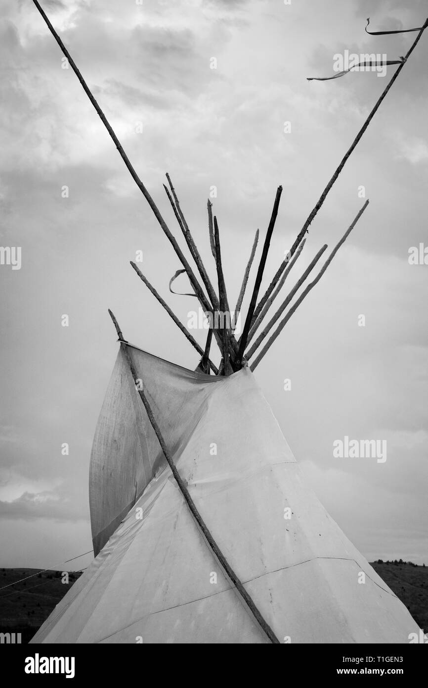 A close up at sunset of the top half of a tipi with dramatic sky in the Western plains in black and white - Stock Image