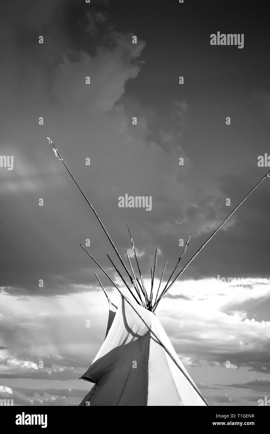 A close cropped view of a tipi with dramatic sky in the Western plains at sunset in the USA in black and white - Stock Image