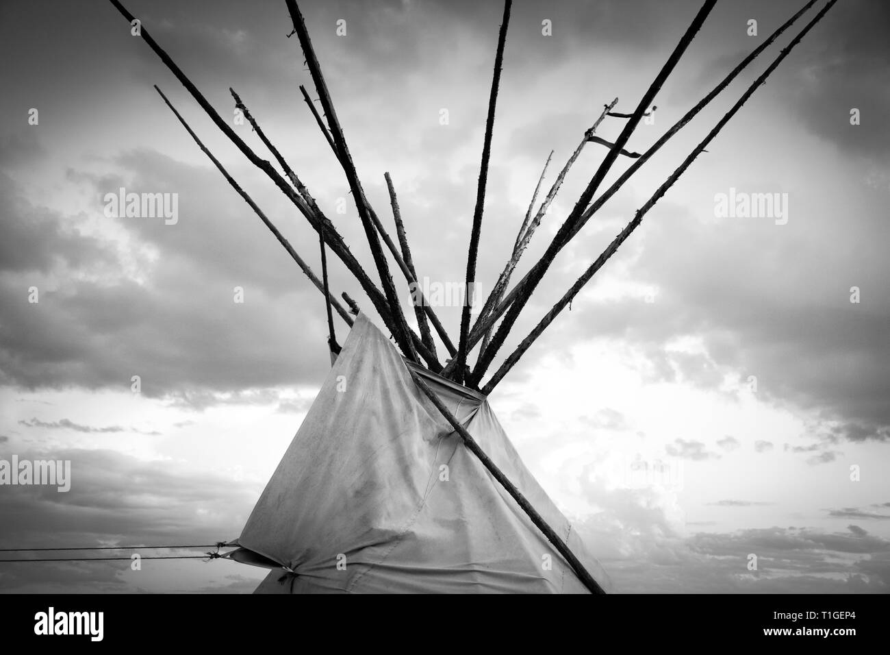 A cropped close up black and white view of the top of a tipi with dramatic sky in the Western plains at sunset in the USA - Stock Image