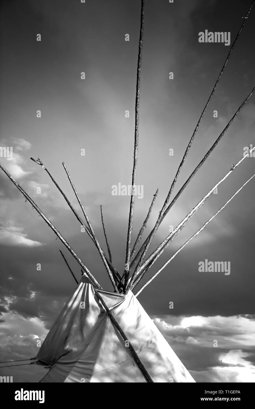 A cropped close up view in black and white of the top of a tipi with dramatic sky in the Western plains at sunset in the USA - Stock Image