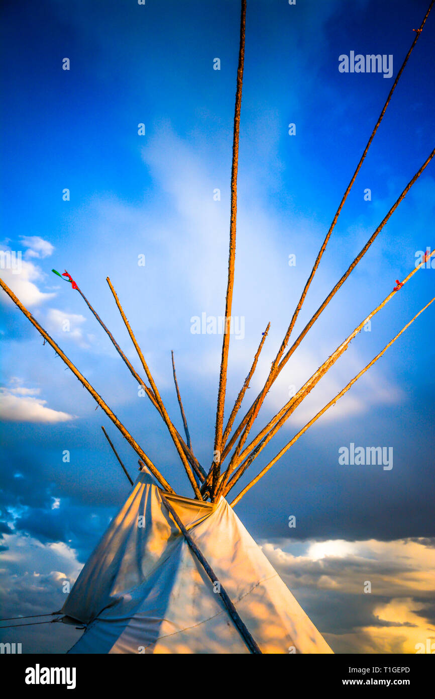 A cropped close up view of the top of a tipi with dramatic sky in the Western plains at sunset in the USA - Stock Image