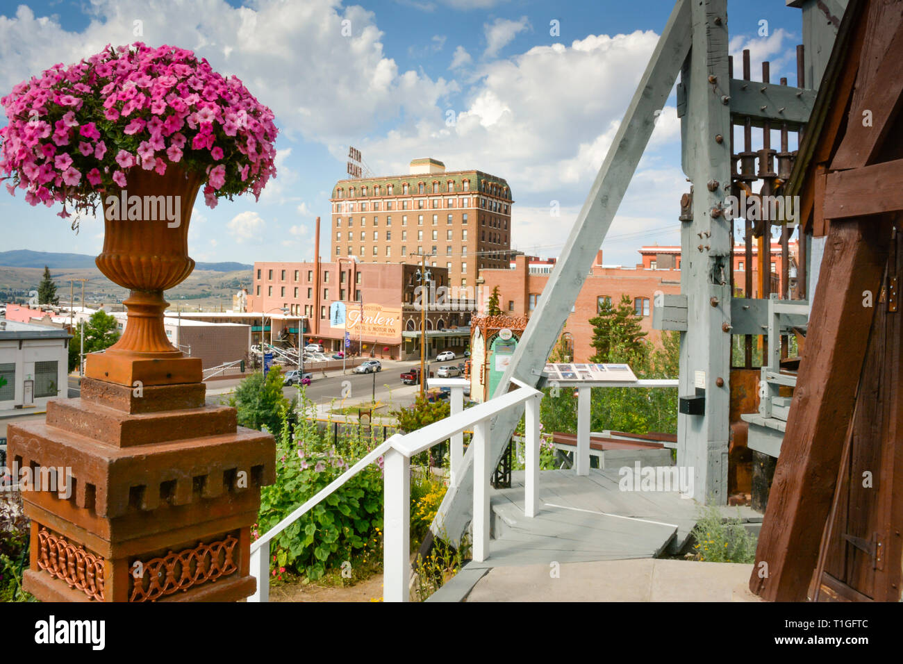 Overlooking downtown from a mine headframe over an old mine shaft, with an historical and commemorative display, with pink petunias in Butte, MT, USA - Stock Image