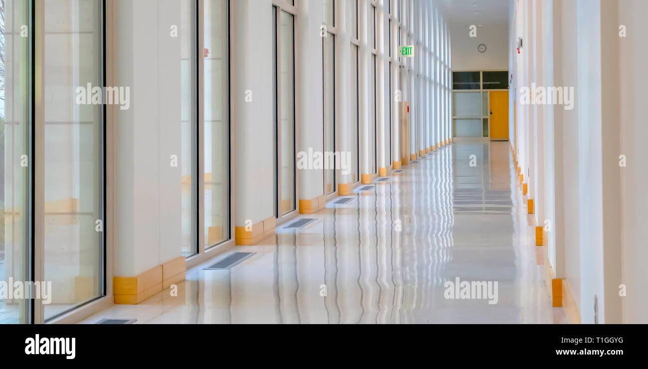 Sunlight streaming inside the hallway of building. Empty long hallway inside a modern modern. Sunlight streams through the glass windows and bounces o - Stock Image