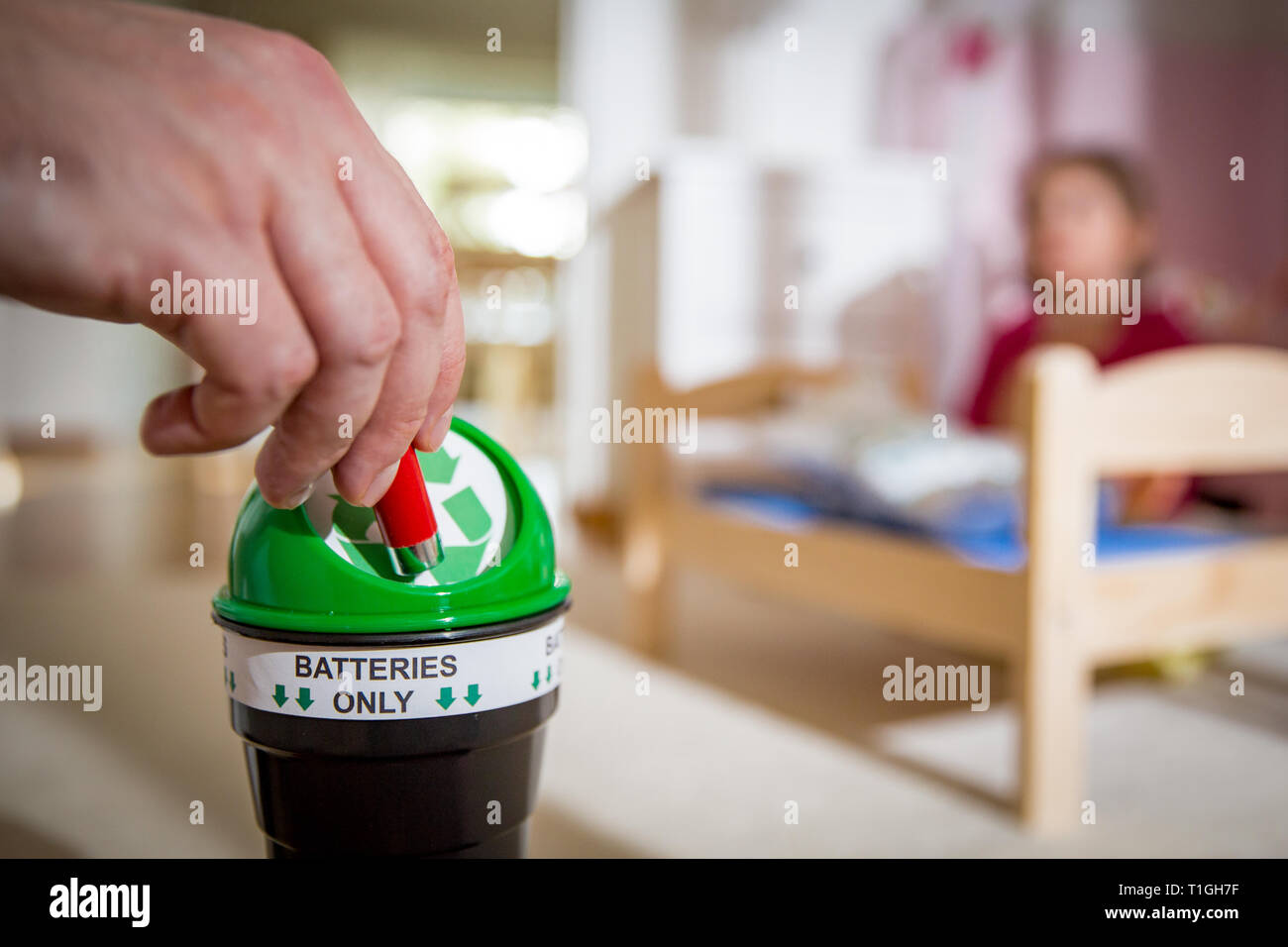 Man putting used batteries into recycling box at home. Child in the nursery room playing with toys. Separating waste concept. Batteries Only. - Stock Image