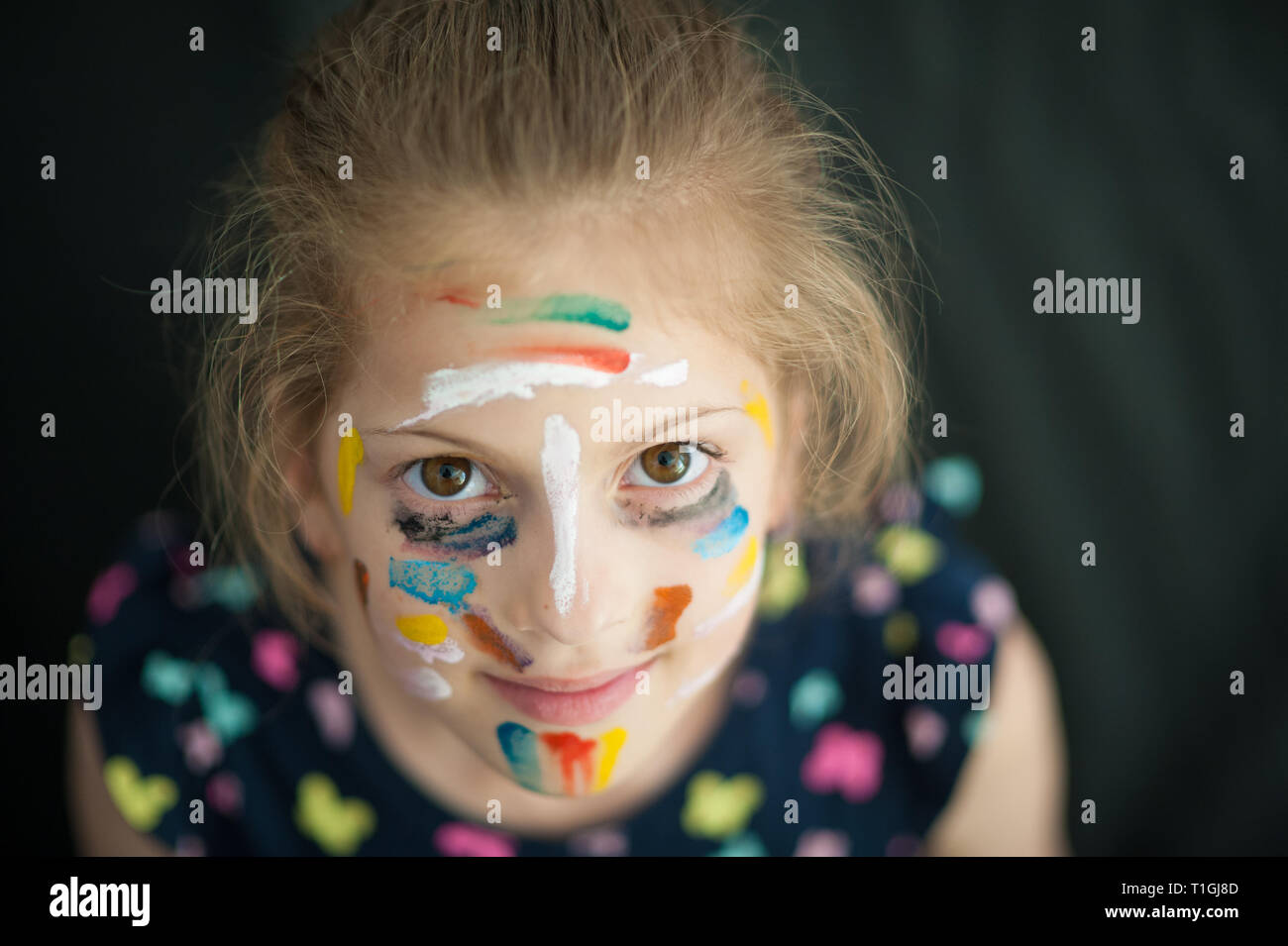 pretty little caucasian girl in multicolored dress with painted colorful face smiling Stock Photo
