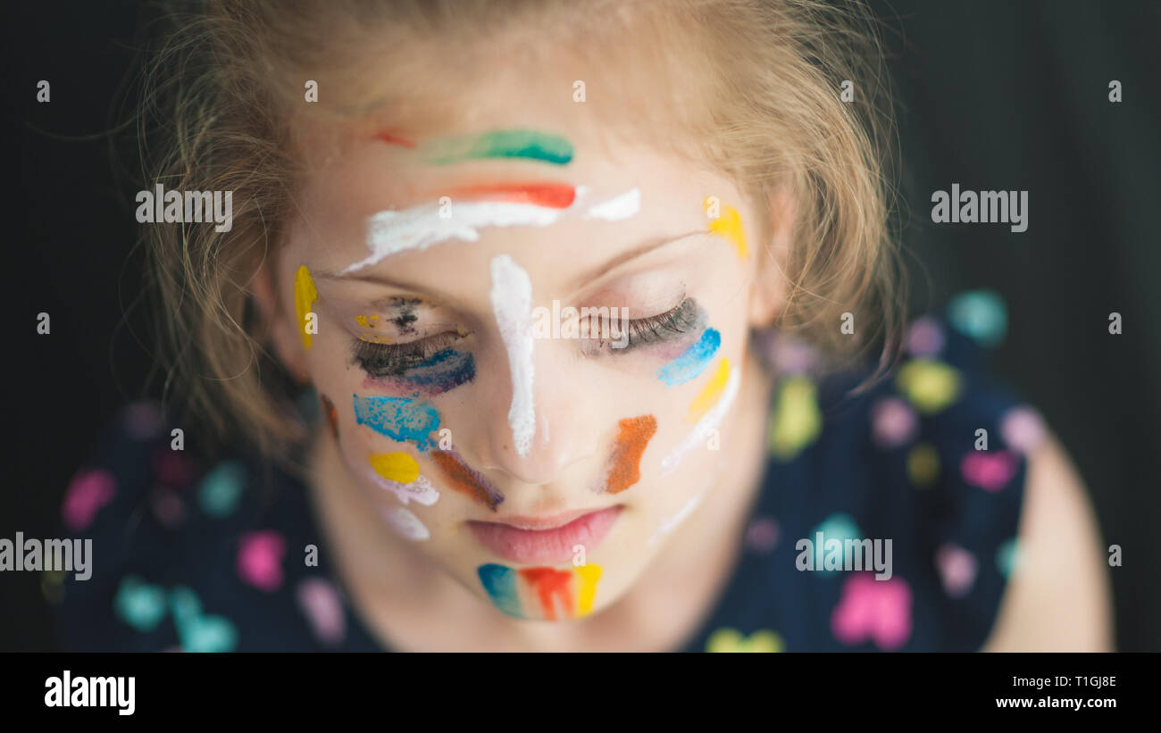 beautiful little girl in multicolored with eyes closed with painted colorful face dreaming Stock Photo
