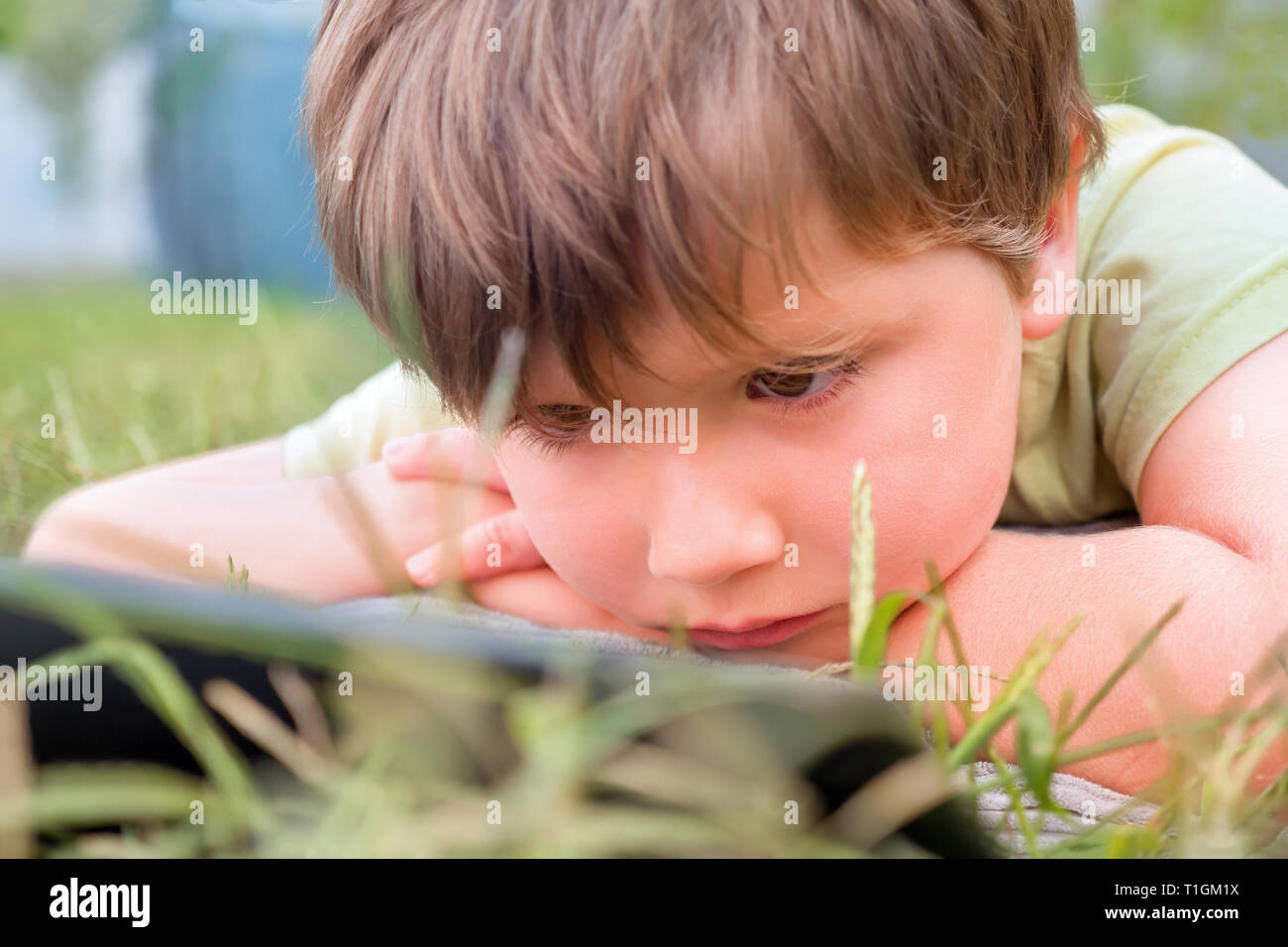 Child with ipad on green grass. Portrait of boy with tablet. Eye problems caused by using tablets too much. Health care concept. Boy with tablet in - Stock Image