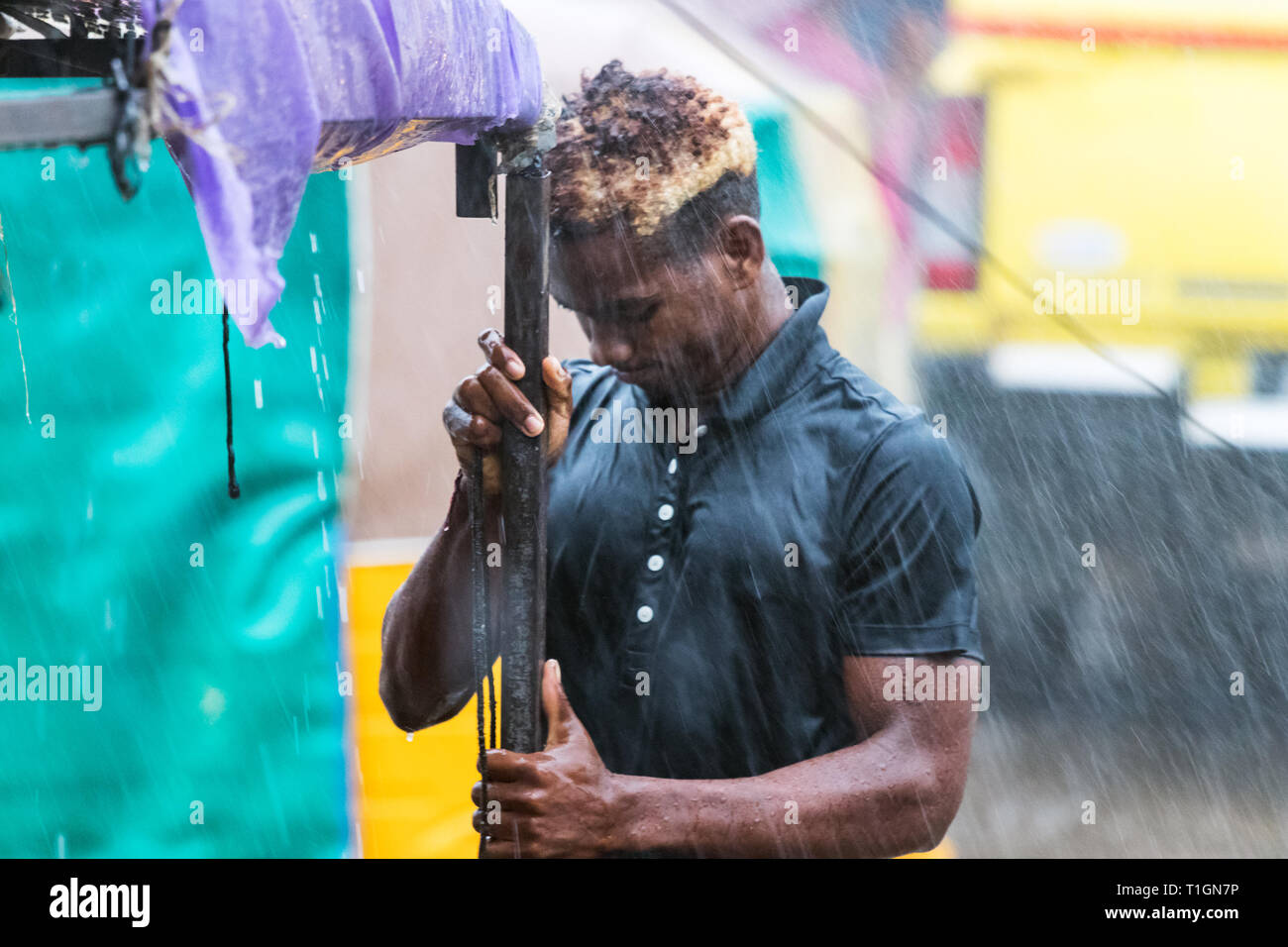 Nosy Be, Madagascar - January 17th, 2019: A man working taking apart his street stall under a heavy rain in Nosy Be, Madagascar. - Stock Image