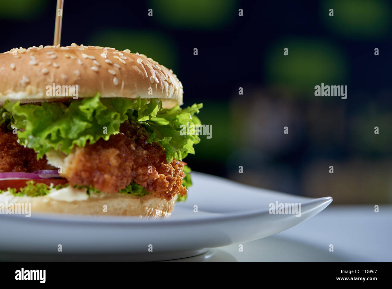 Closeup of juicy burger with fried chicken, fresh vegetables, greens and sesame staying on the plate in cafe. Big tasty sandwich cooked for eating. Concept of fast food and cuisine. - Stock Image