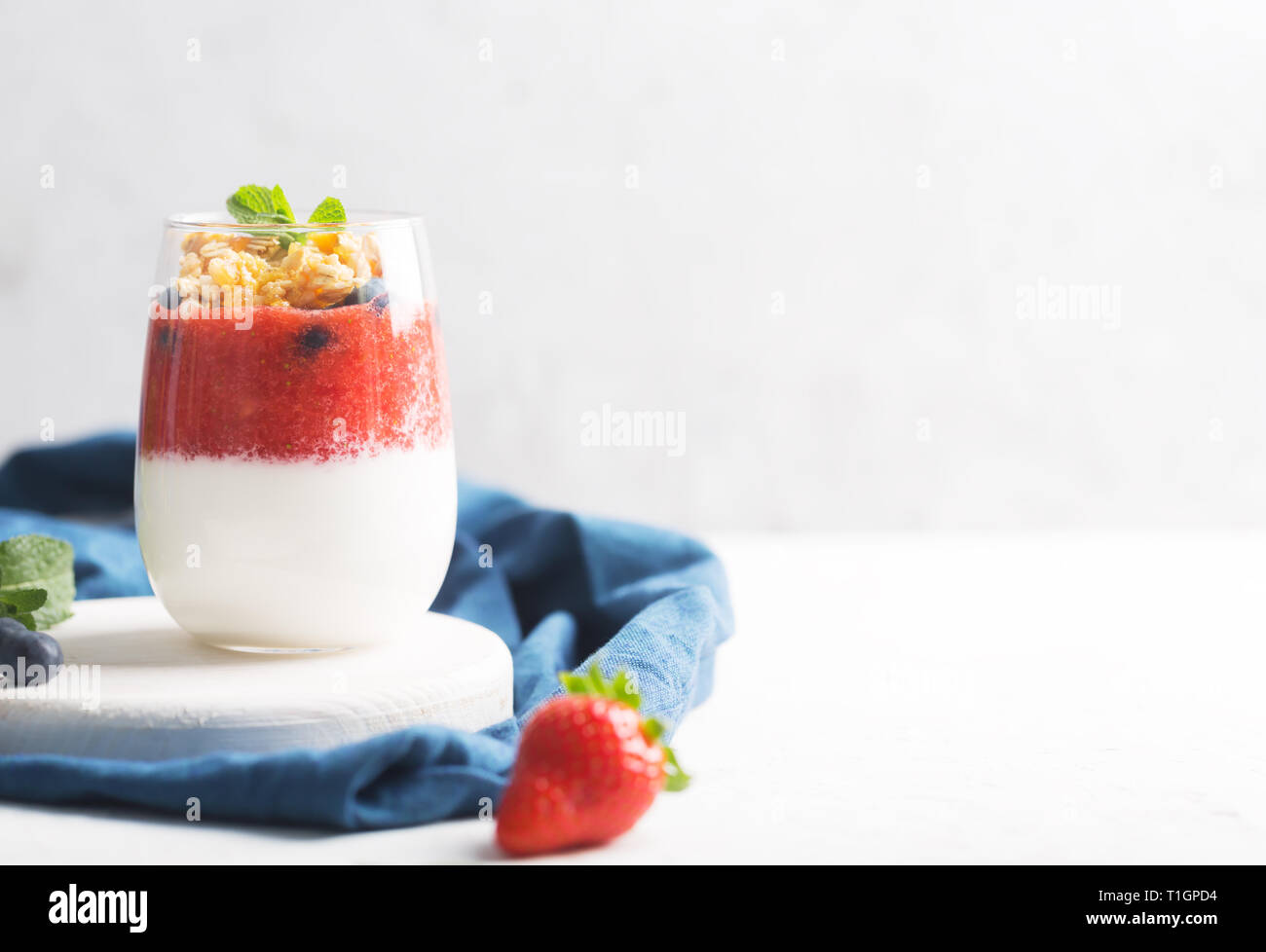 Glass of yogurt or panna cotta with strawberry mousse and granola on a white background - Stock Image