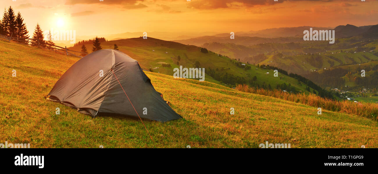 Camping in the autumn mountains under rising sun - Stock Image