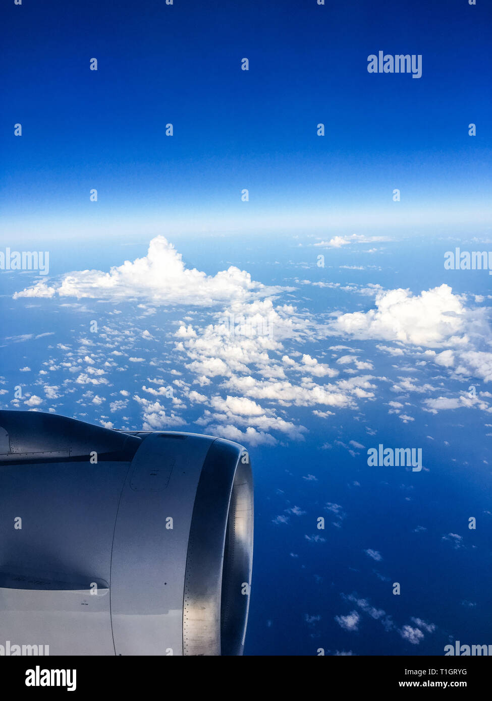Travel, cloudscape and natural environment concept - View from the airplane window, sky and ocean blue Stock Photo