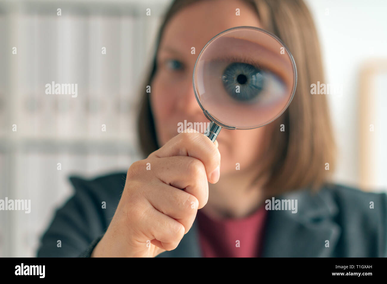 Businesswoman with magnifying glass doing business financial auditing, examination and evaluation of financial statements. - Stock Image