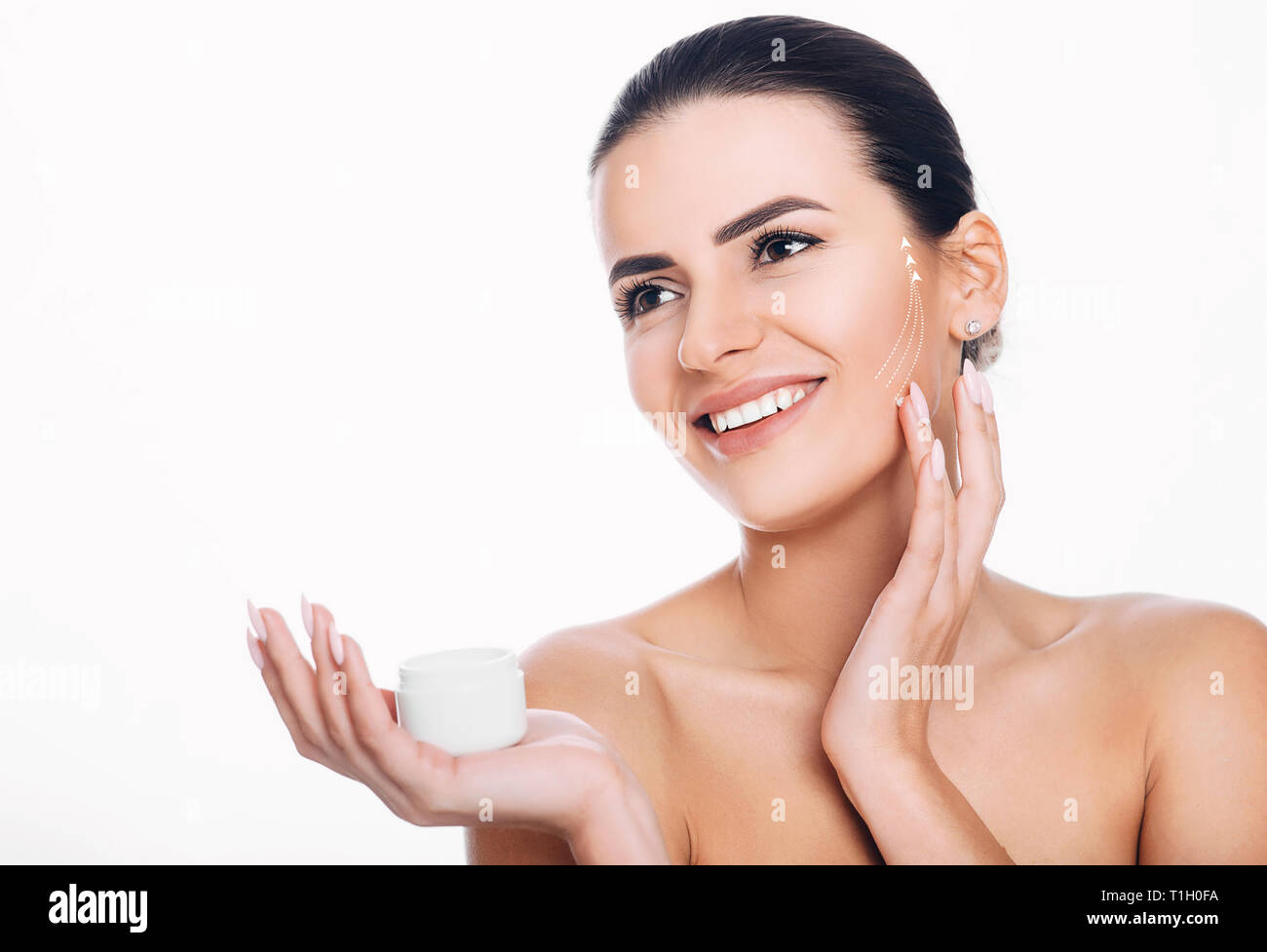 smiling woman with lifting arrows on face applying moisturizer on skin. Concept of moisturizer skin lifting - Stock Image