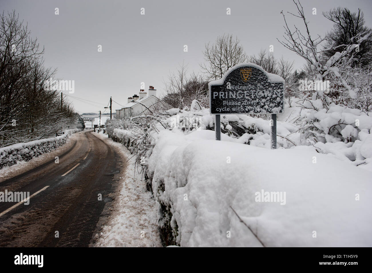 Princetown village sign covered in snow beside slush covered road Stock Photo