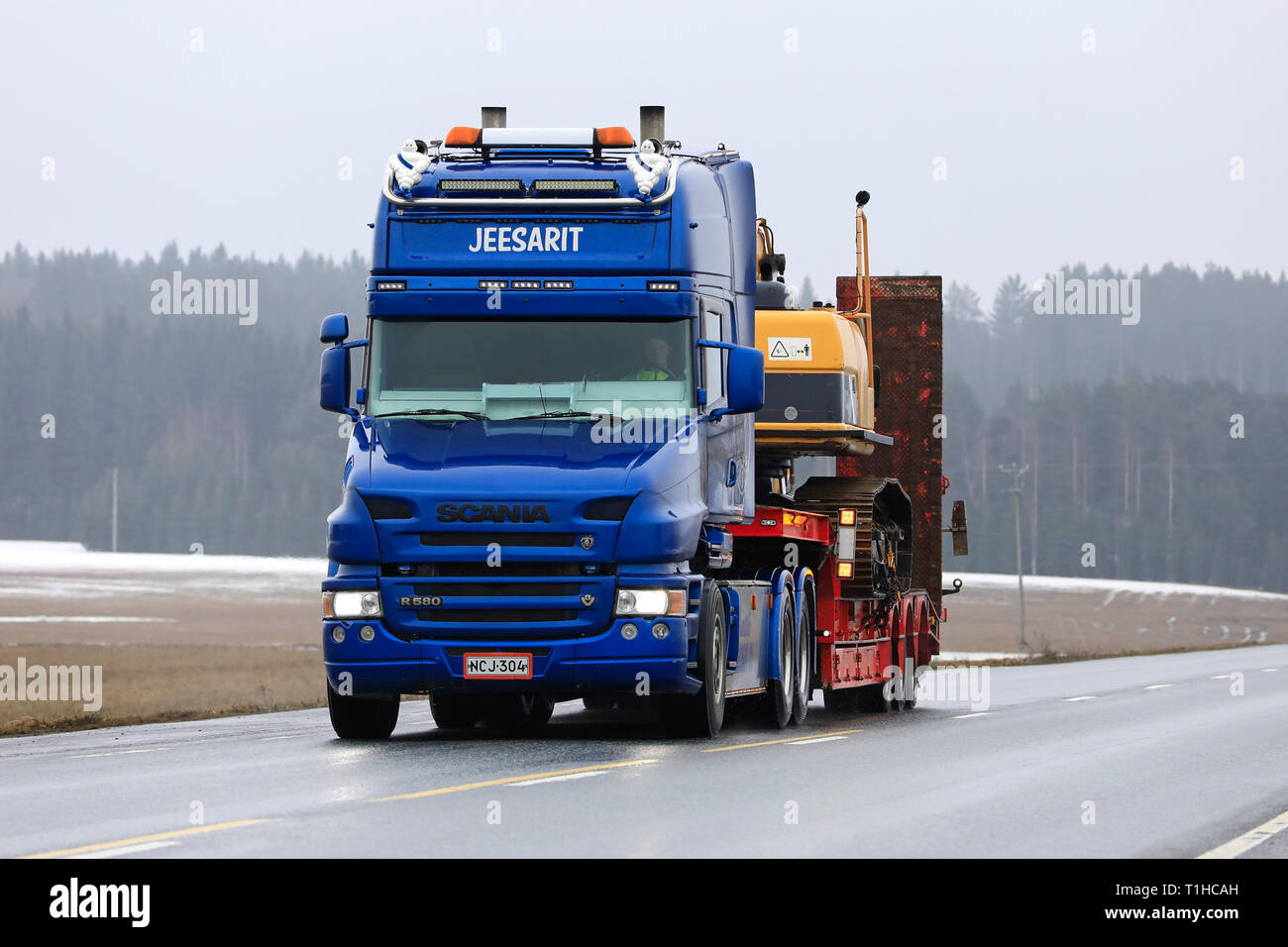 Jokioinen, Finland - March 23, 2019:  Blue Scania R580 conventional cab of Maansiirto Jeesarit Oy hauls tracked excavator on trailer along highway. - Stock Image