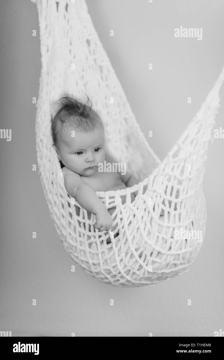 Newborn Baby relaxing in a white hammock with soft bright background - happy family moments - Stock Image