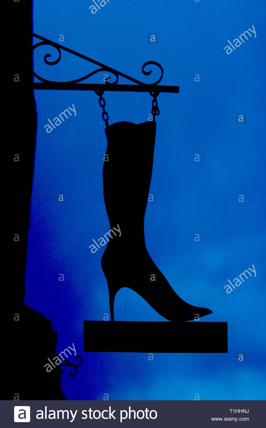 Stylised silhouette on blue of a lady's high-heeled, knee-length boot suspended from a wrought iron bracket by two short lengths of chain. Copy space - Stock Image