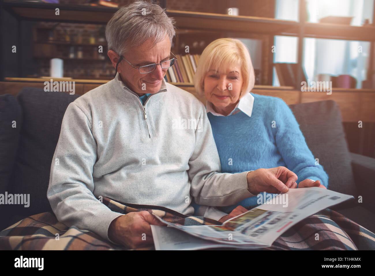 Beautiful old couple are sitting on the couch together and readi - Stock Image