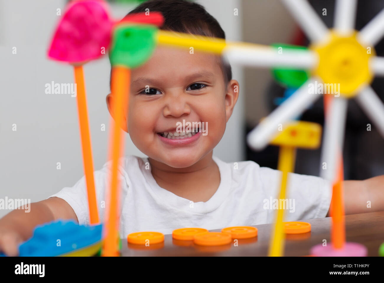 A hispanic boy with big smile while he plays with colorful building toys and learns to count with elementary manipulative toys. - Stock Image