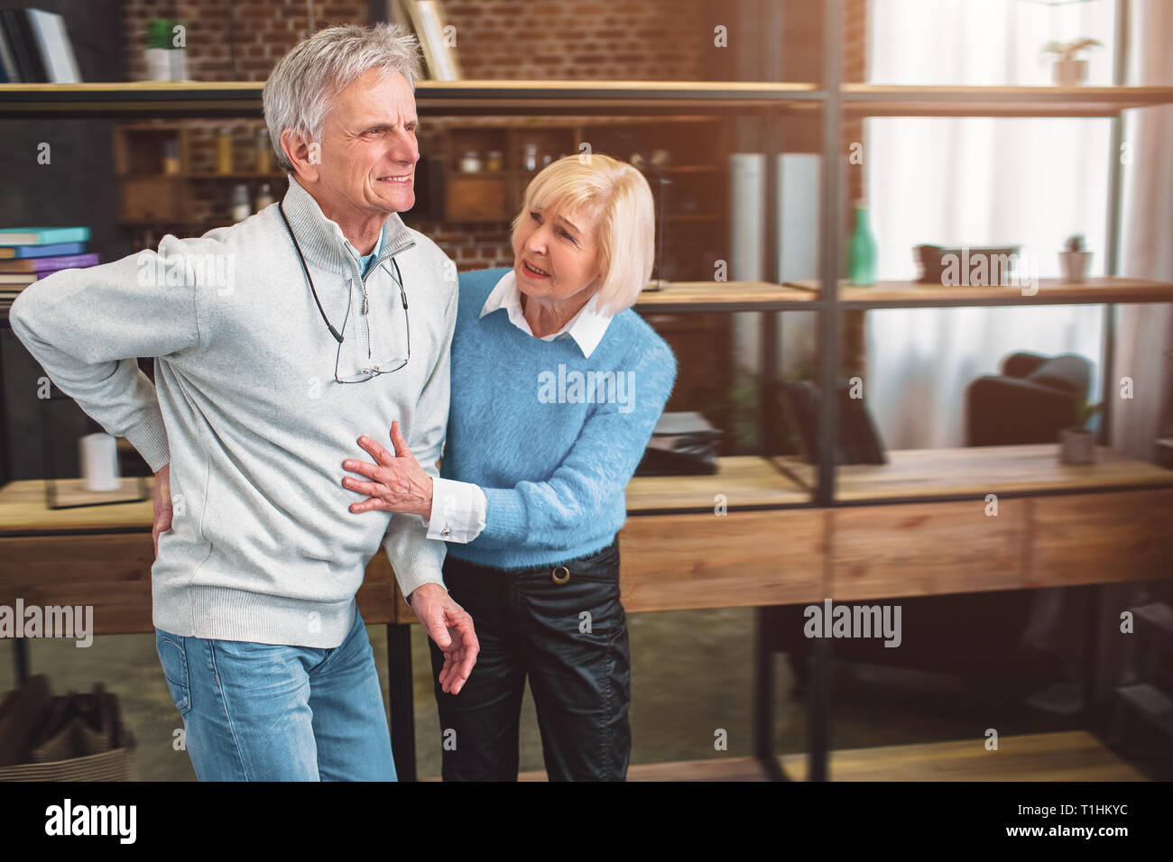A picture of old man keeping his hand on the back. He has a pain - Stock Image