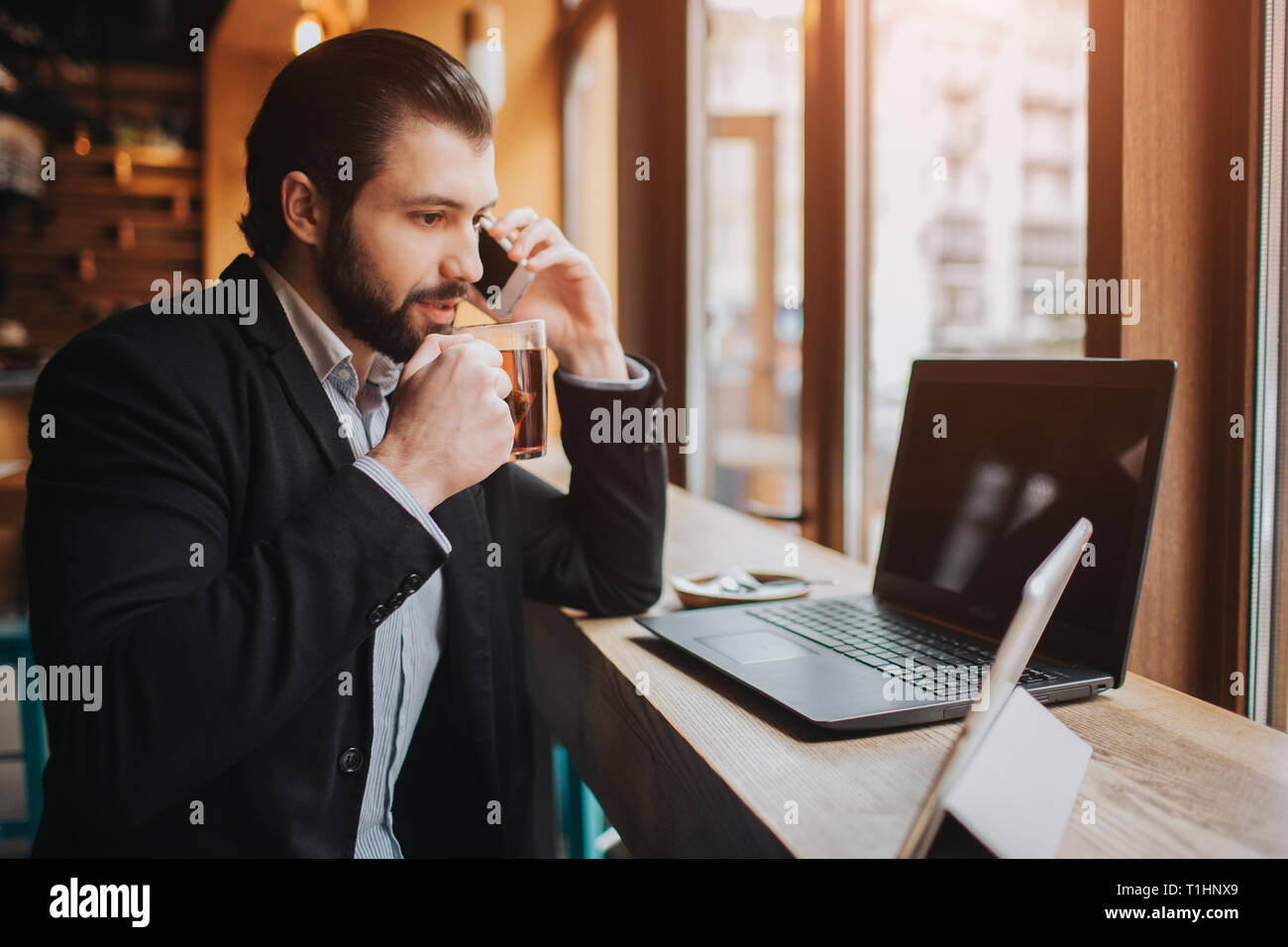 Busy man is in a hurry, he does not have time, he is going to eating and working. Worker eating, drinking coffee, talking on the phone, at the same - Stock Image