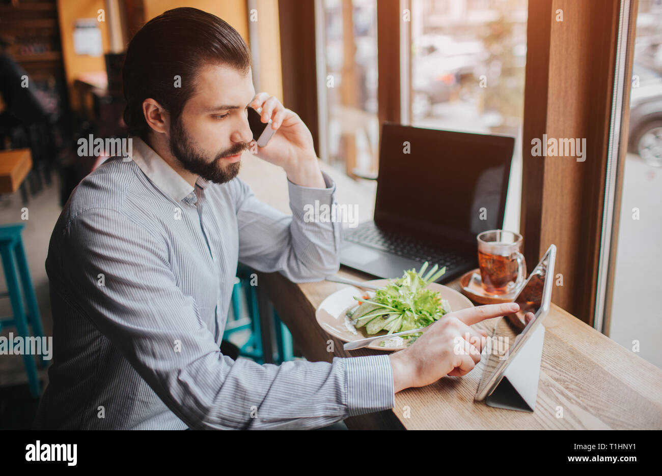 Busy man is in a hurry, he does not have time, he is going to eating and working. Worker eating, drinking coffee, talking on the phone, at the same Stock Photo