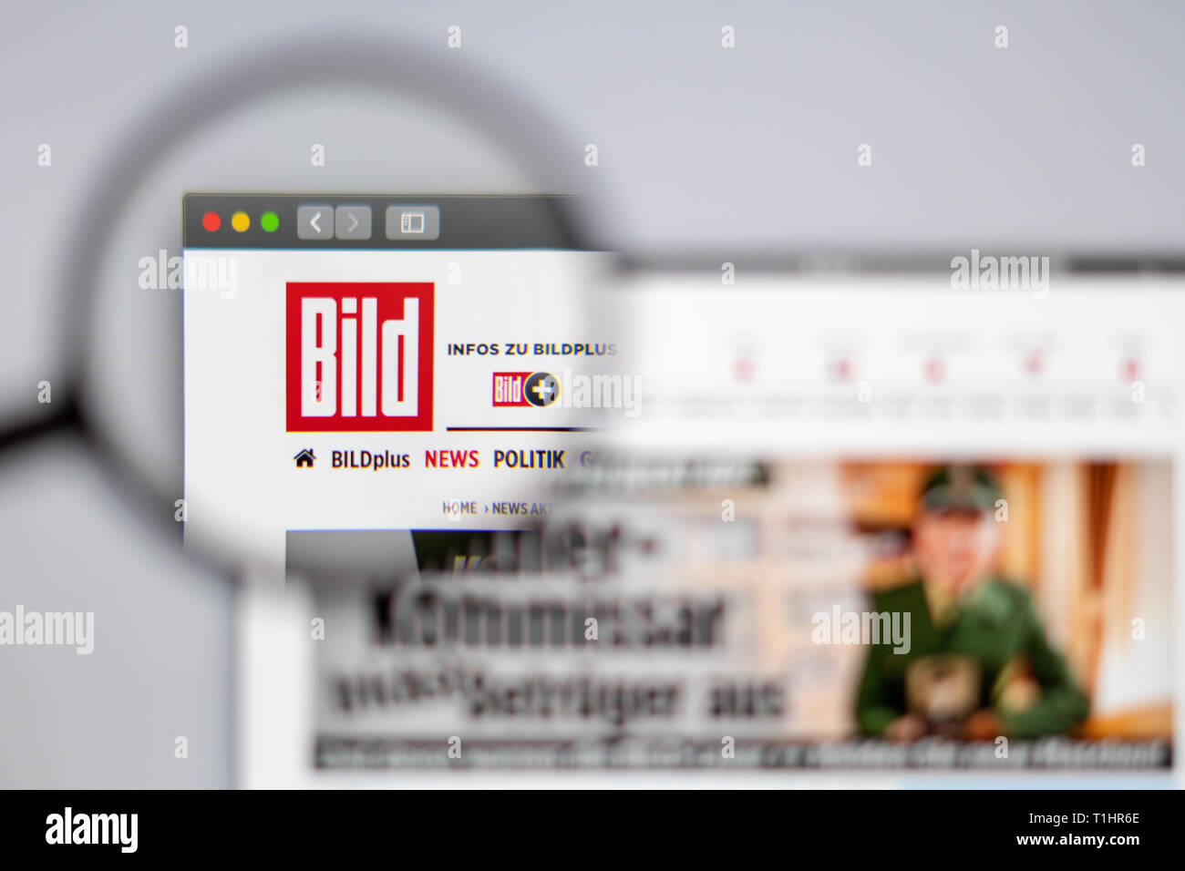 Germany news media Bild website homepage. Bild logo visible  through a magnifying glass. - Stock Image
