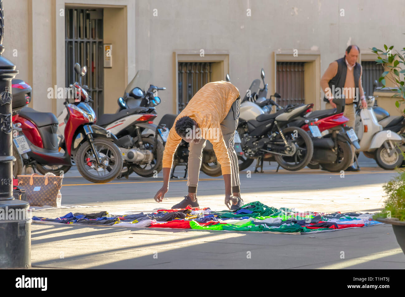 Seville, Spain - March 9, 2019: African immigrant selling their