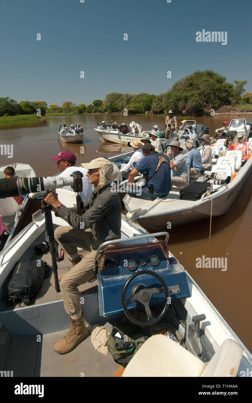 Photographers in boats waiting for a jaguar to wake up in The Pantanal in Brazil - Stock Image