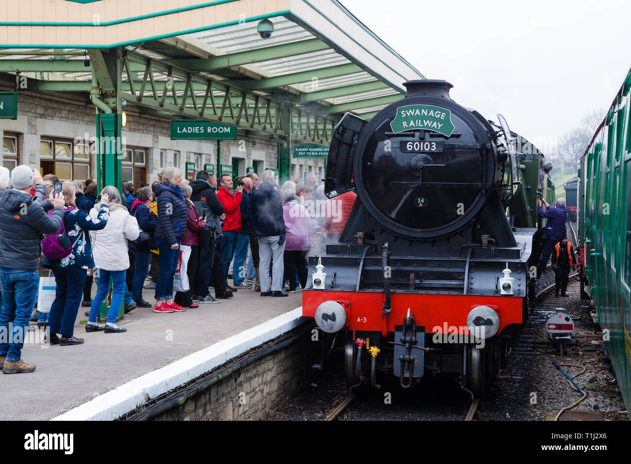 Steam locomotive The Flying Scotsman stops at Swanage Railway station as crowds gather to take photographs. Stock Photo