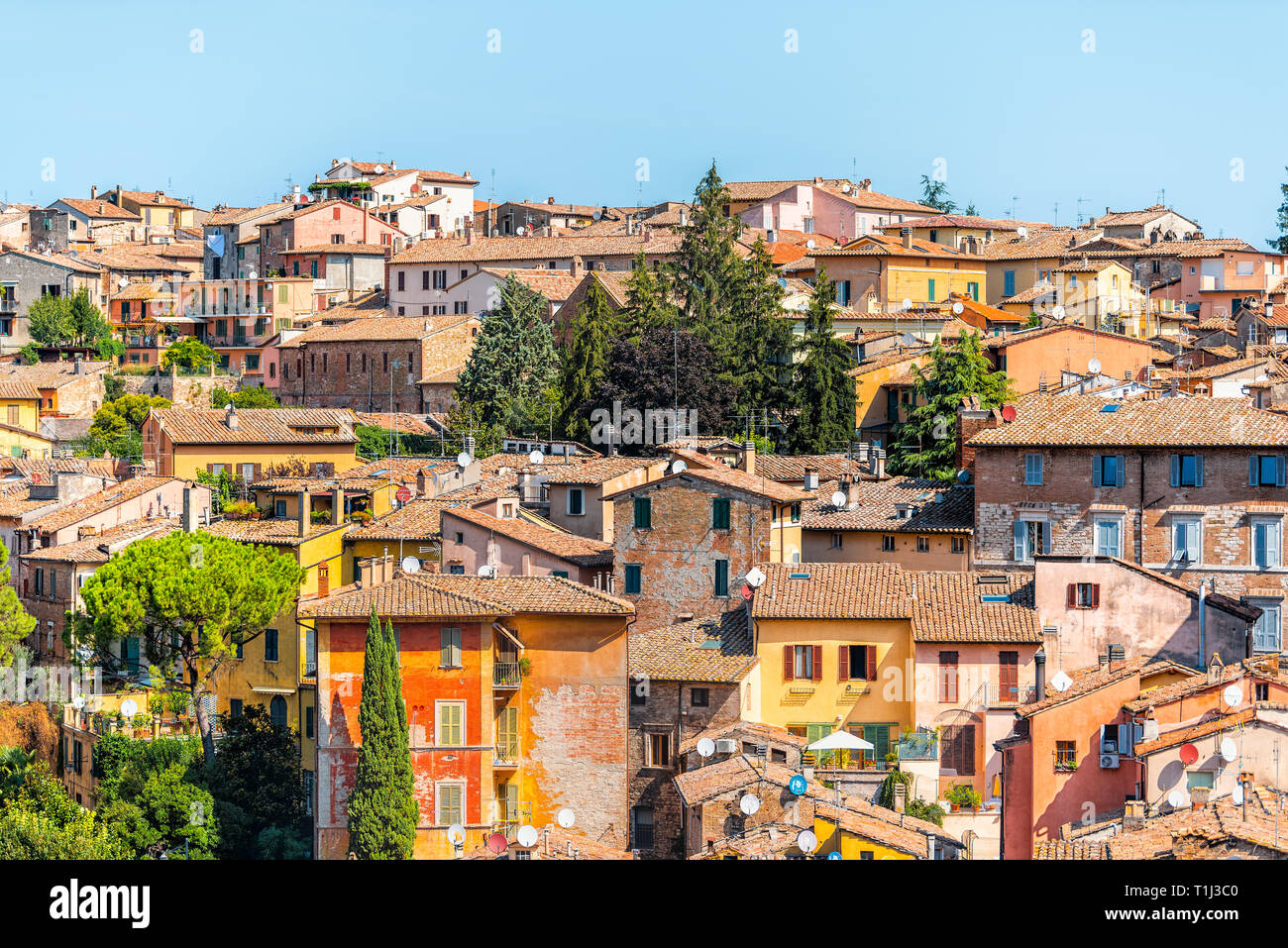 Perugia, Italy Umbria cityscape with historic old medieval Etruscan buildings and rooftops of town village yellow orange colors in summer satellite di - Stock Image