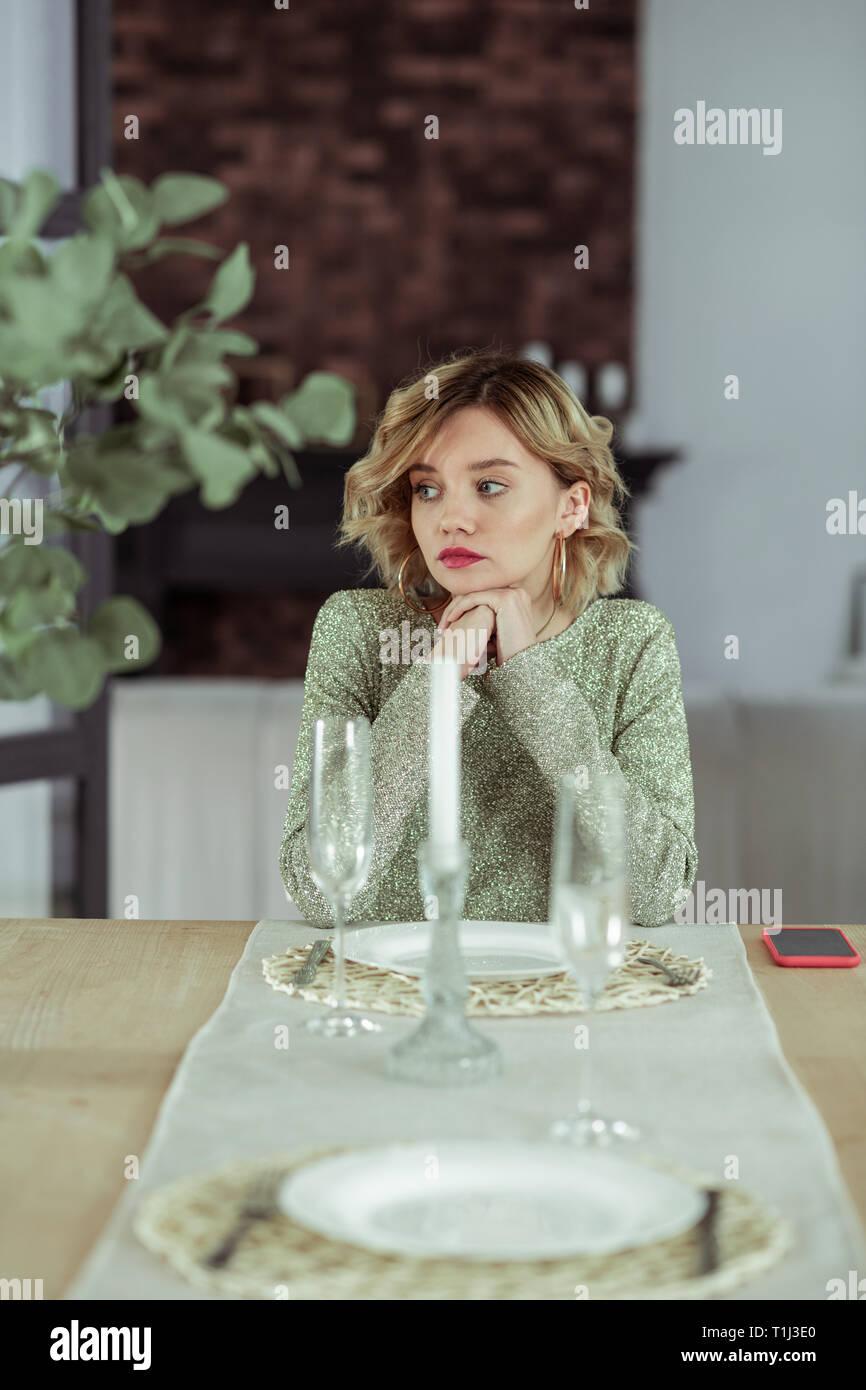 Appealing young girlfriend feeling heartbroken sitting alone - Stock Image