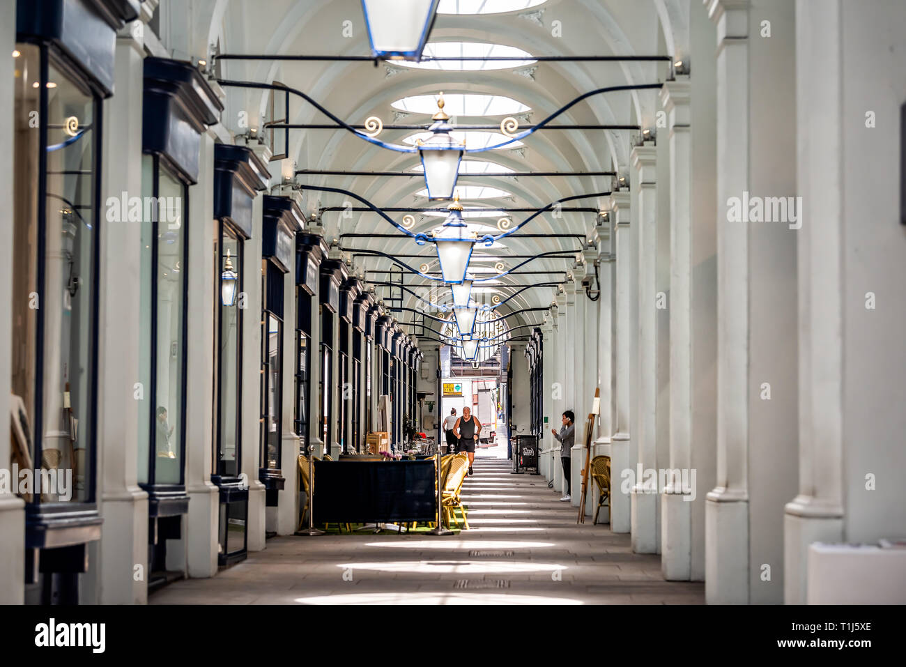London, UK - June 22, 2018: Empty shopping shop passage tunnel with man exercising jogging on Piccadilly sidewalk street road in center of downtown ci - Stock Image