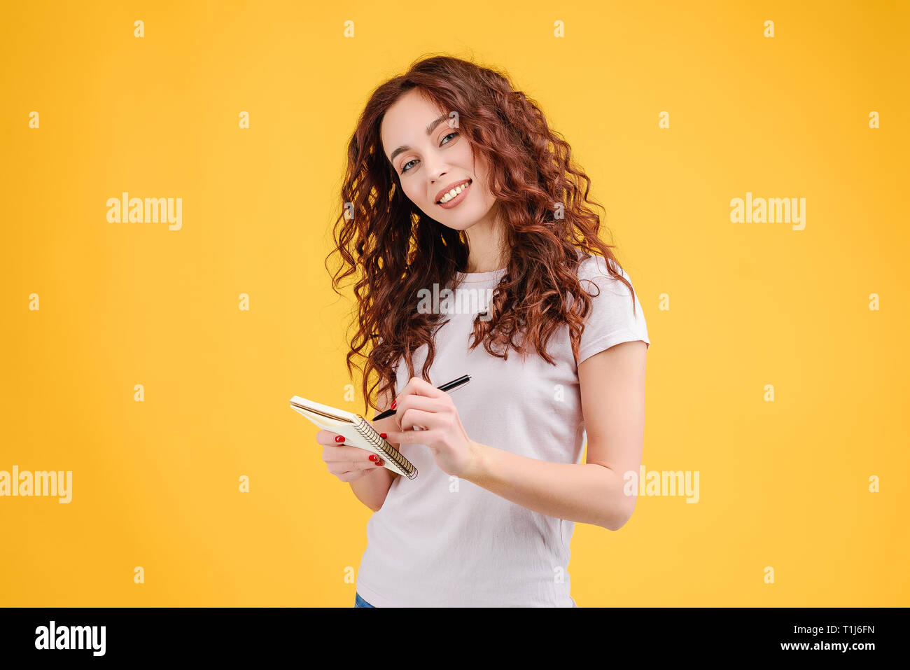 Attractive brunette girl with curly hair isolated over yellow background with a notebook and a pen in her hands making notes about new classes. Studie Stock Photo