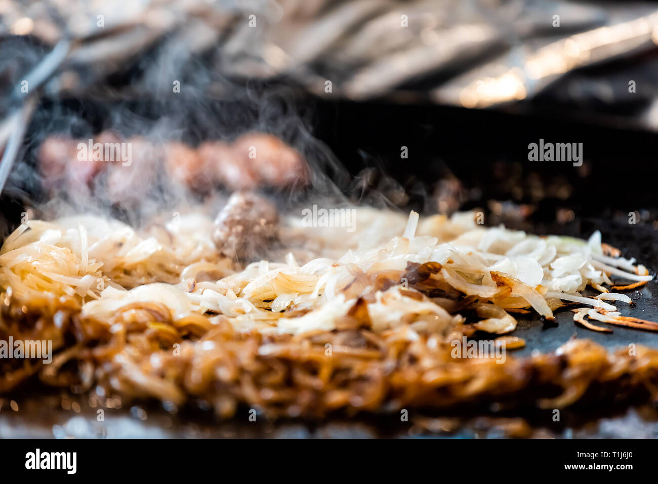 Fast food counter grill background with cooking fresh onions beef pork meat in truck hot steam closeup and nobody - Stock Image