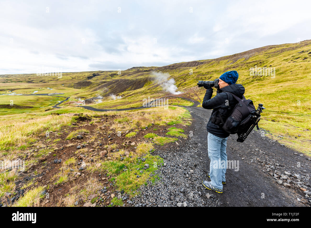 Reykjadalur, Iceland Hveragerdi Hot Springs road footpath with steam landscape morning in golden circle with man and camera tripod on hiking trail - Stock Image