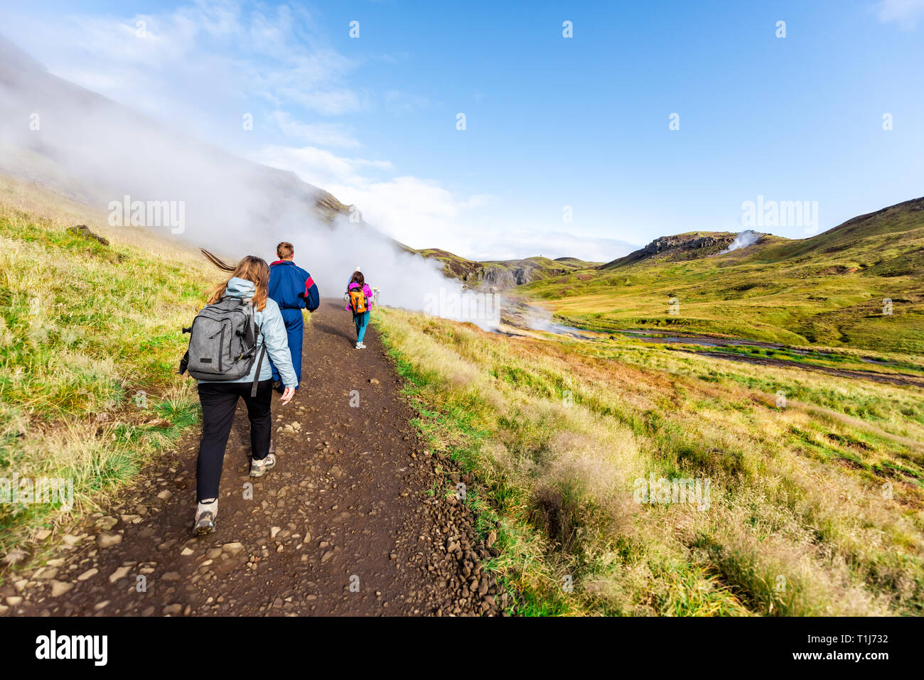 Hveragerdi, Iceland - September 18, 2018: Reykjadalur Hot Springs road trail with steam fumarole vent during autumn day in golden circle with people o - Stock Image