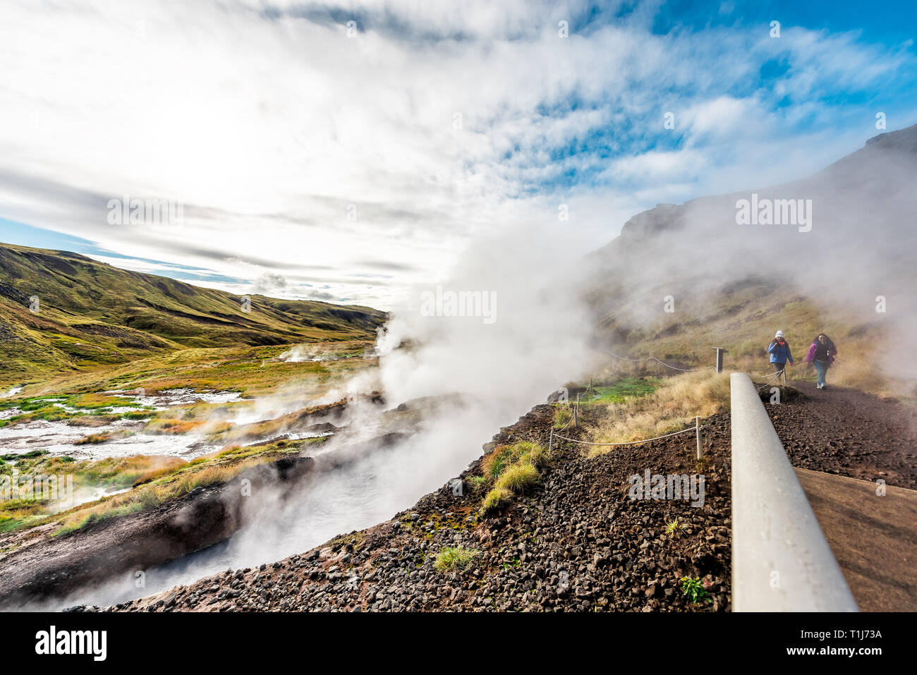 Hveragerdi, Iceland - September 18, 2018: Reykjadalur Hot Springs road trail with with people on trail and vapor steam fumarole vent during autumn day - Stock Image