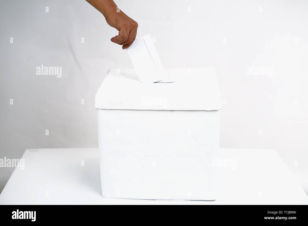 The hand putting a ballot in the ballot box - Stock Image