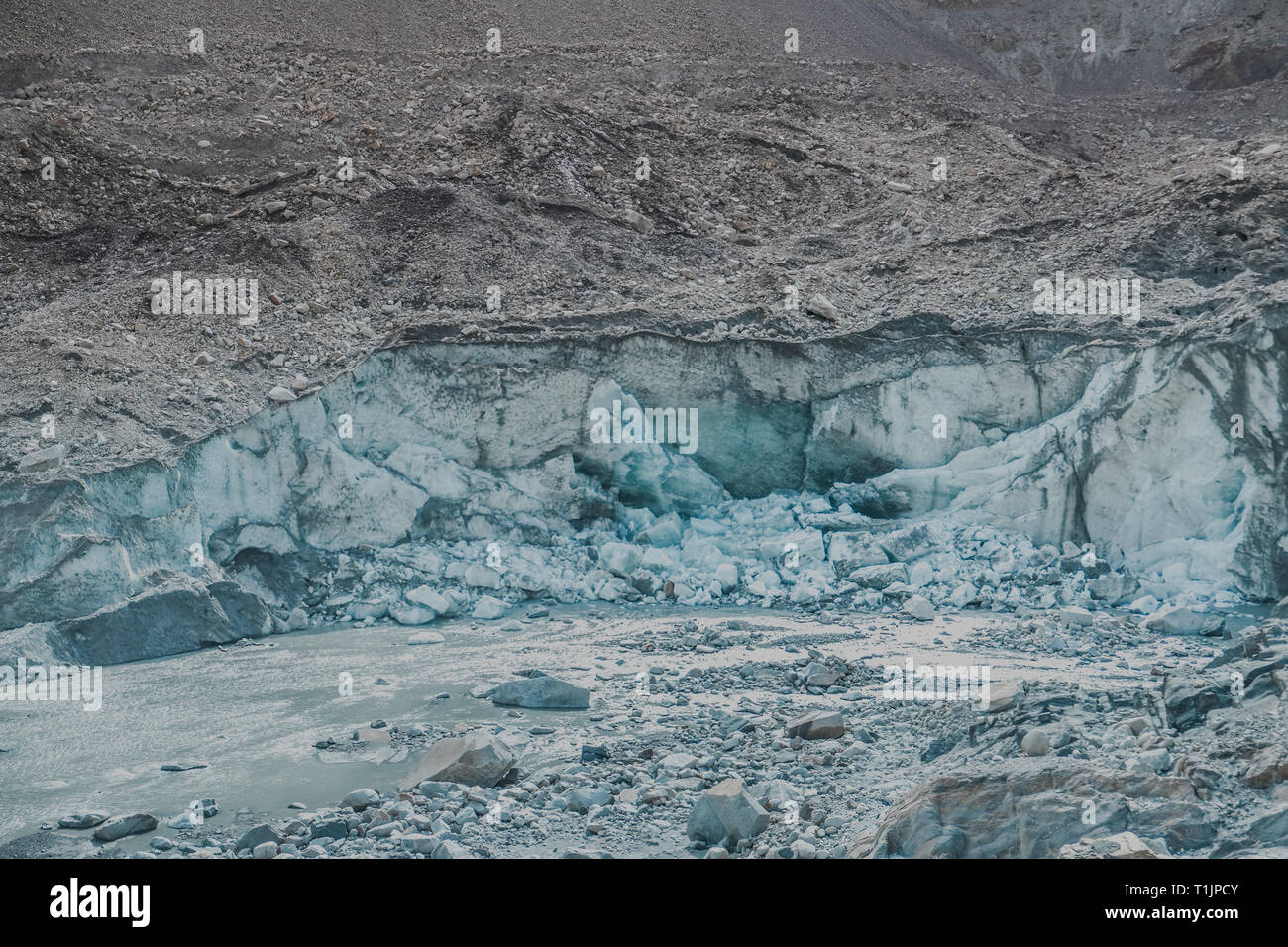 Cracking and melting of Passu glacier. The glacial surface is covered with rubble, boulders and mud. Gojal, Upper Hunza. Gilgit Baltistan, Pakistan. - Stock Image