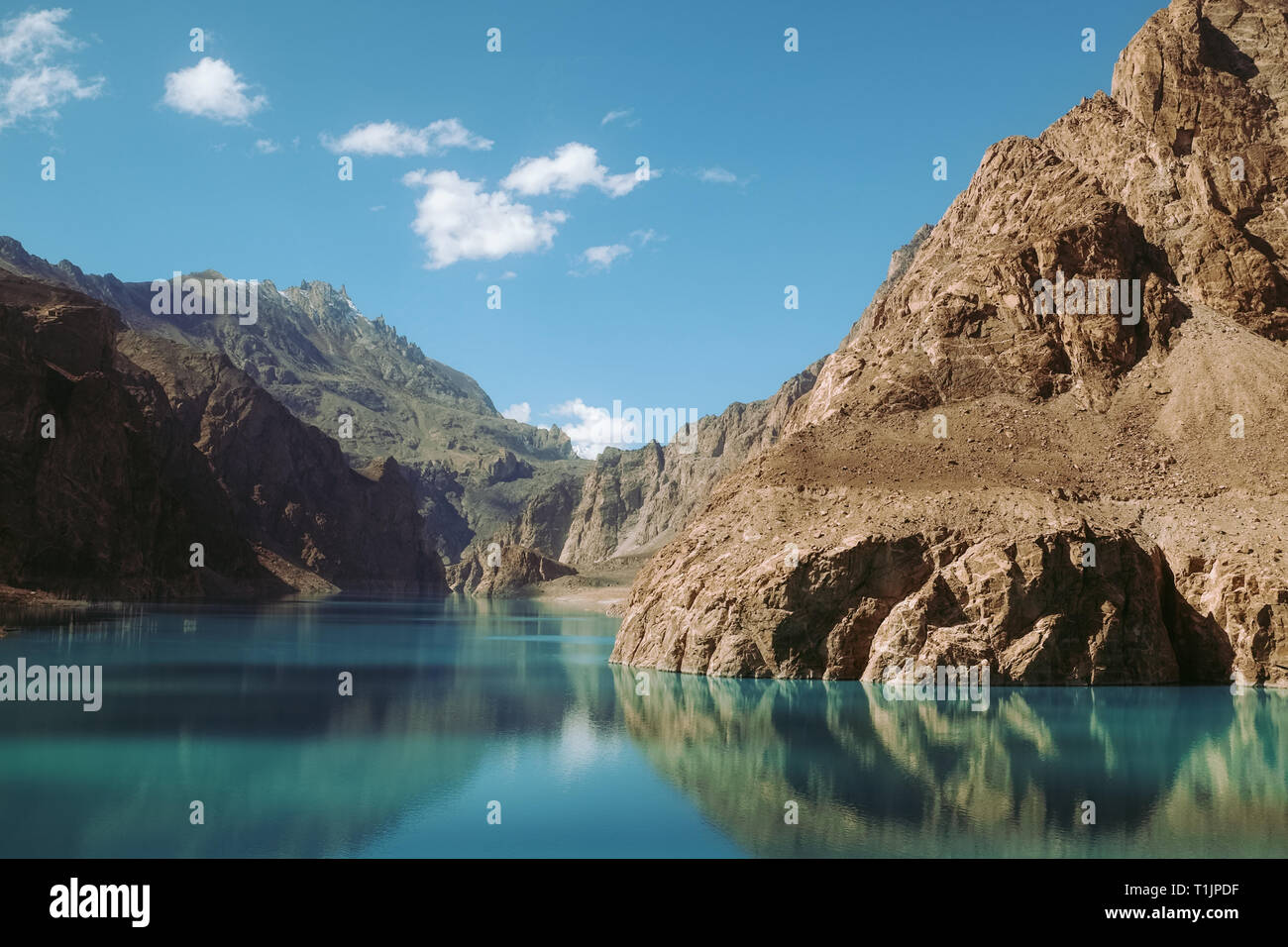 reflection in the water of Attabad Lake, surrounded by mountains in Karakoram range. Gojal Hunza, Gilgit Baltistan, Pakistan. - Stock Image