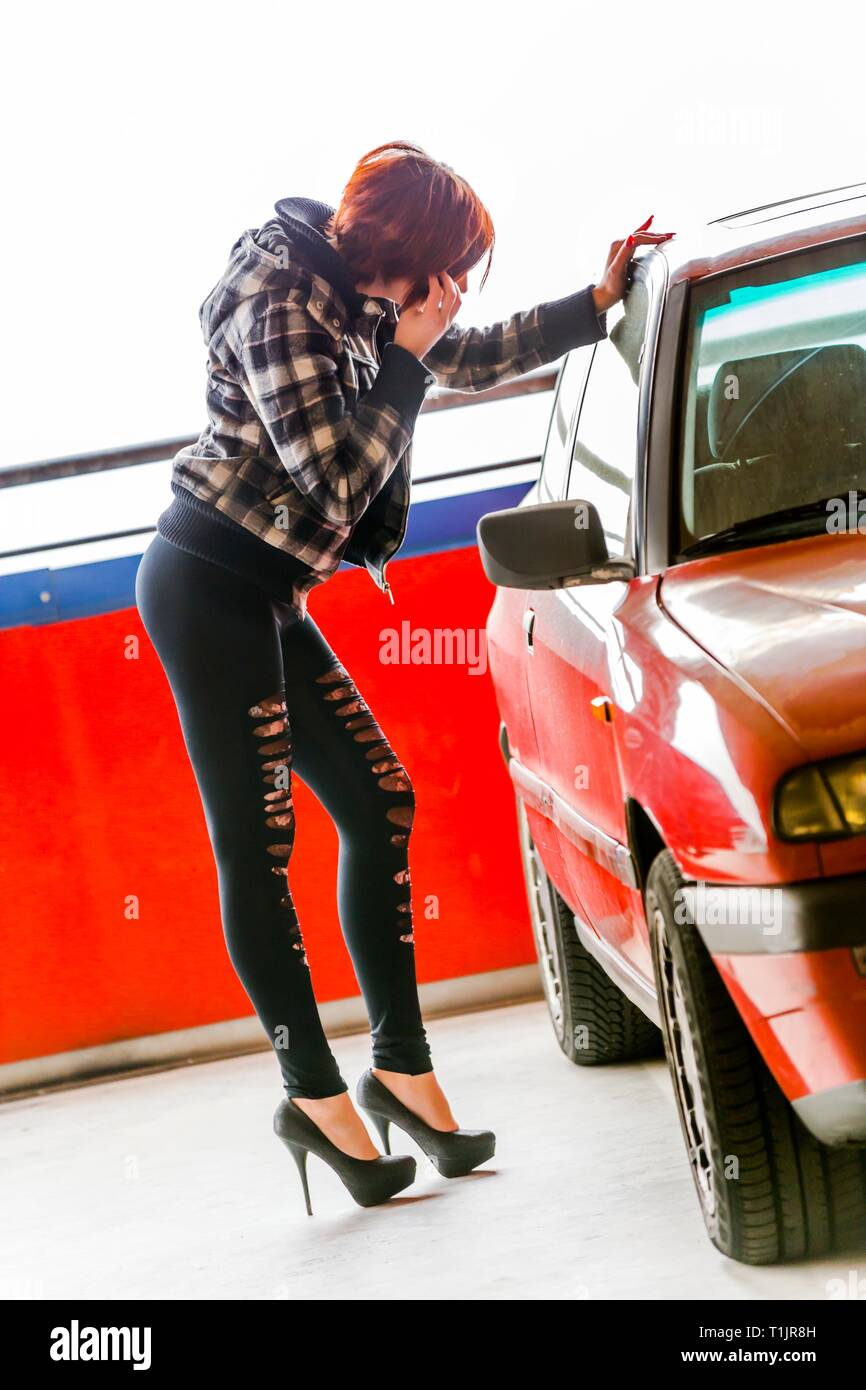 Pretty teen girl legs heels admiring herself e.g. fixing facial makeup by looking at car window reflection - Stock Image