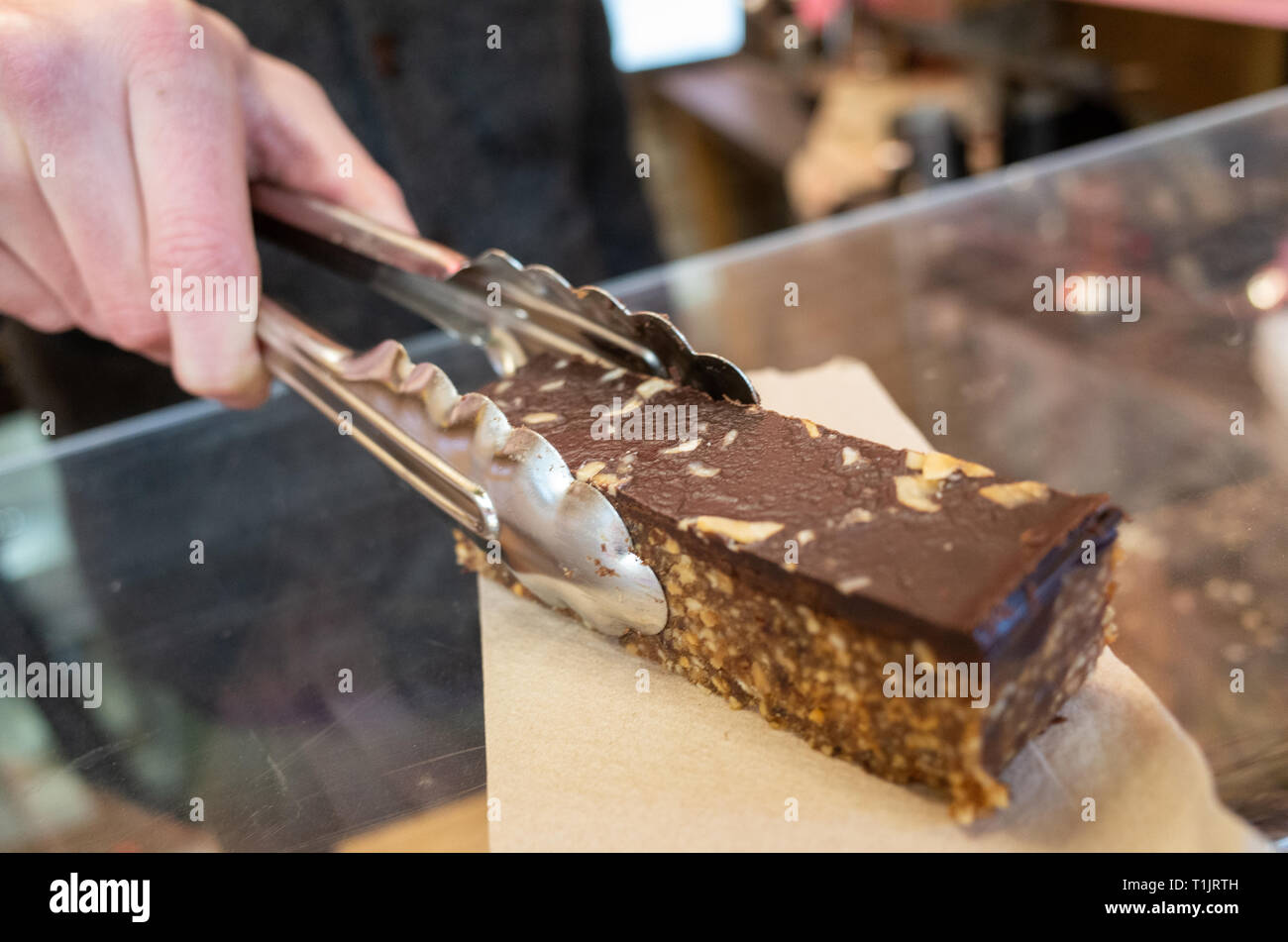 CARDIFF, UNITED KINGDOM.  17 January 2019.  Sam Thomas of Hardlines coffee shop serves up a vegan Snickers themed homemade chocolate granola bar in an - Stock Image