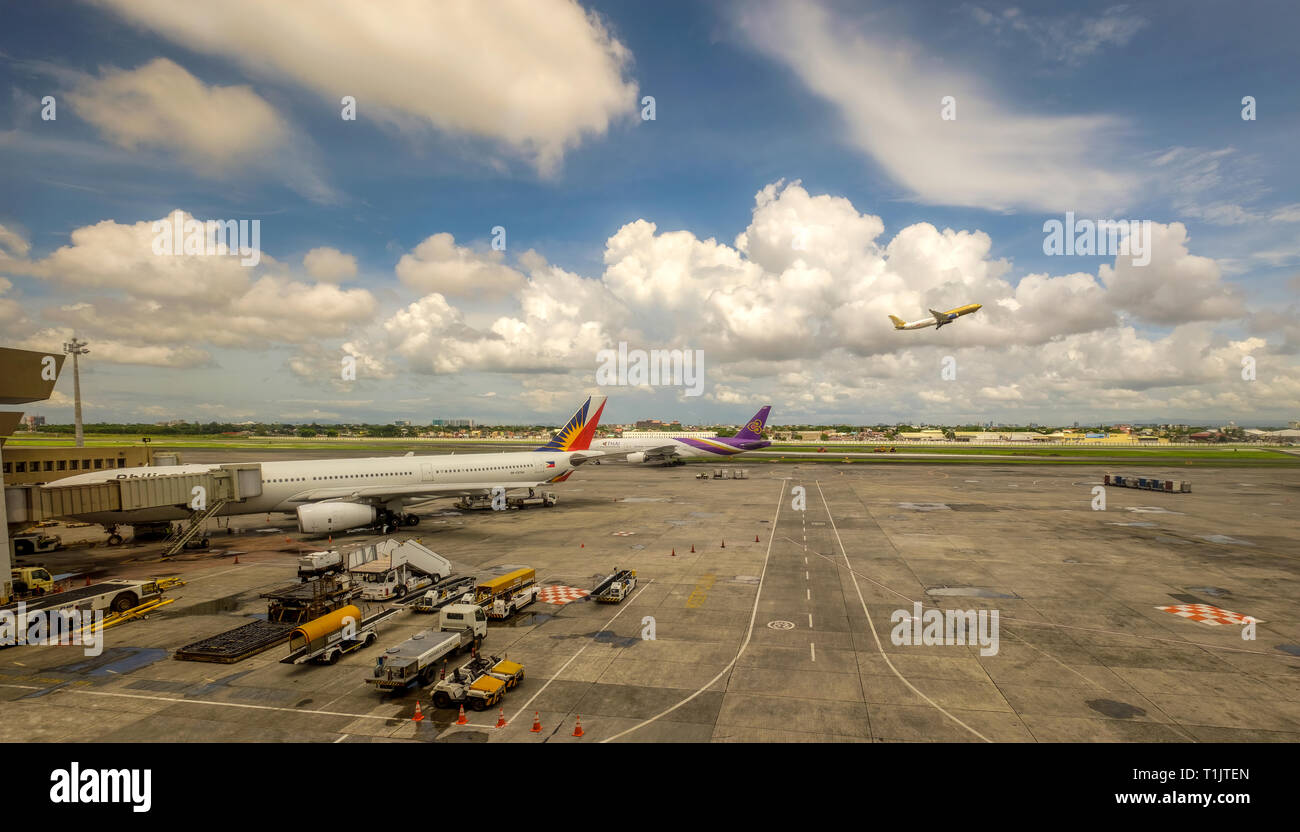 The busy scene at Kuala Lumpur  International Airport with am airplane taking off as others are refueled and deliver or pick-up passengers - Stock Image