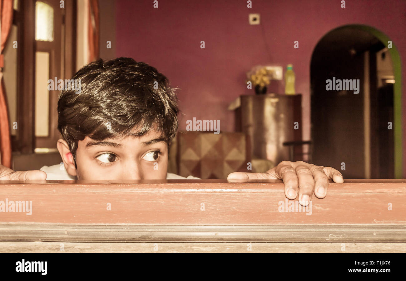 Young boy curiously looking outside through a window. - Stock Image